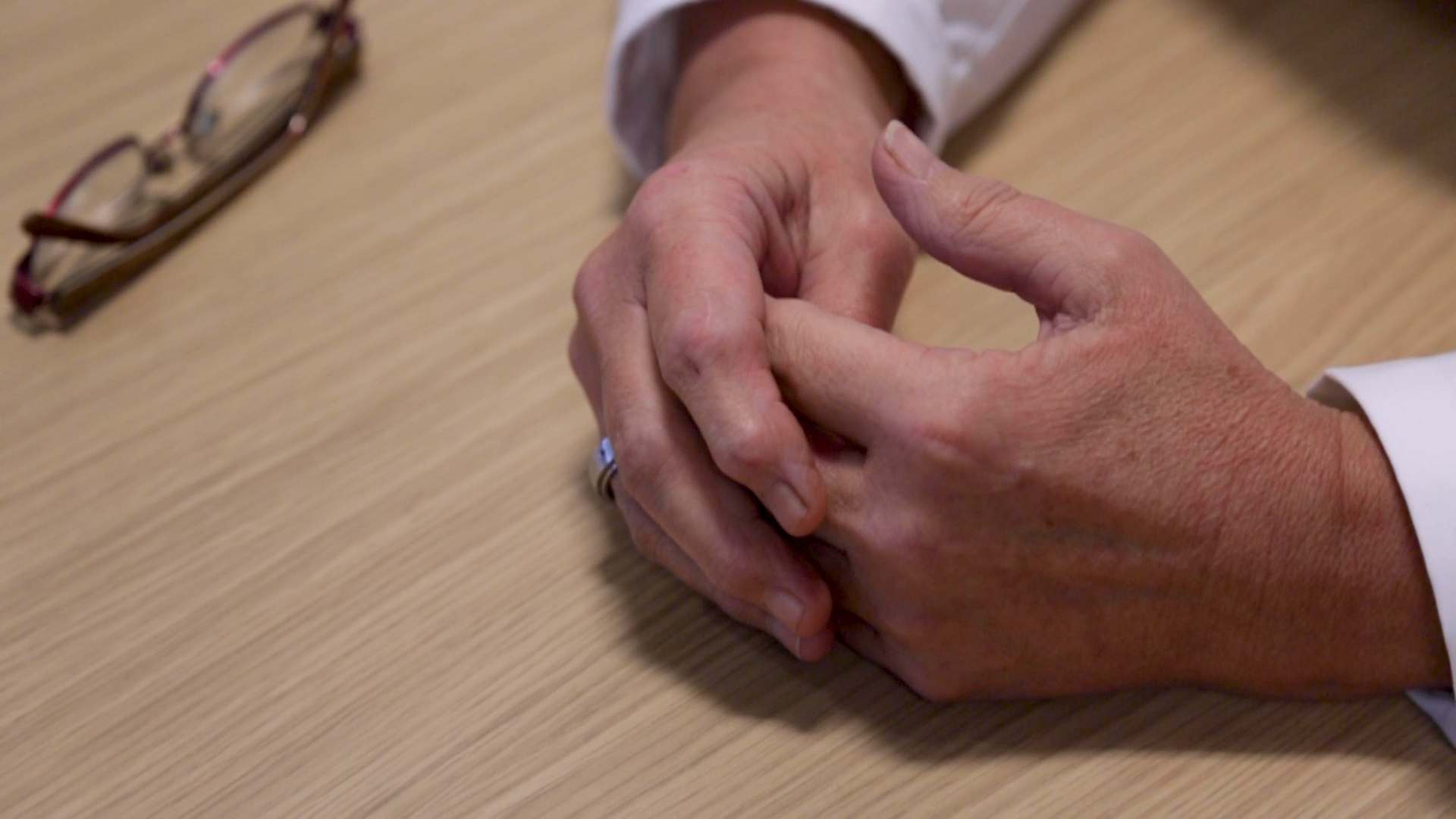 Anxious hands rest on a wood table