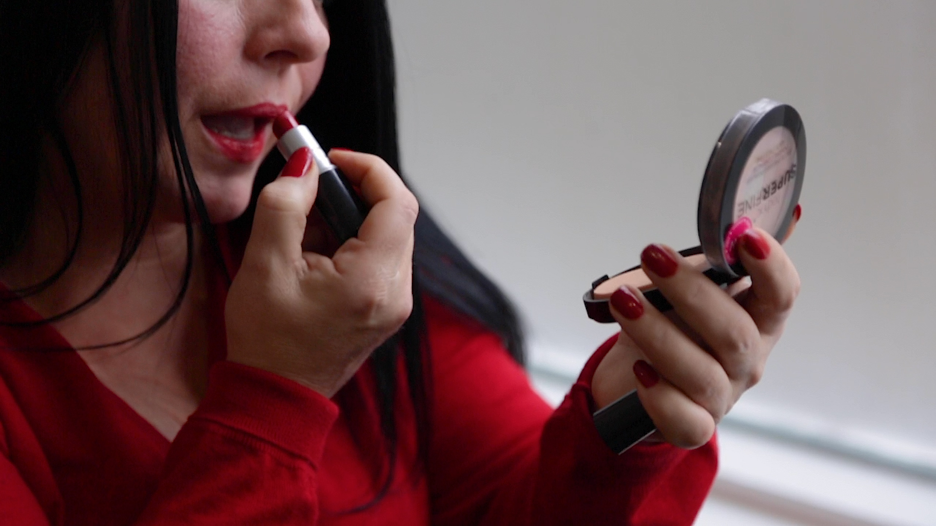 A person applies make-up in a handheld mirror