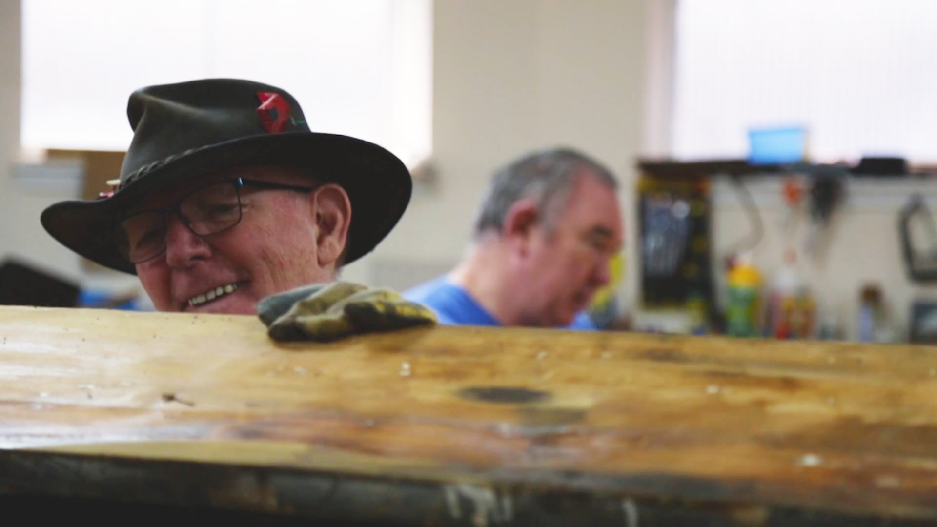 An older person in a hat smiles while working in a carpentry workshop