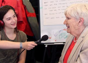 A young person with a microphone interviews an elderly person