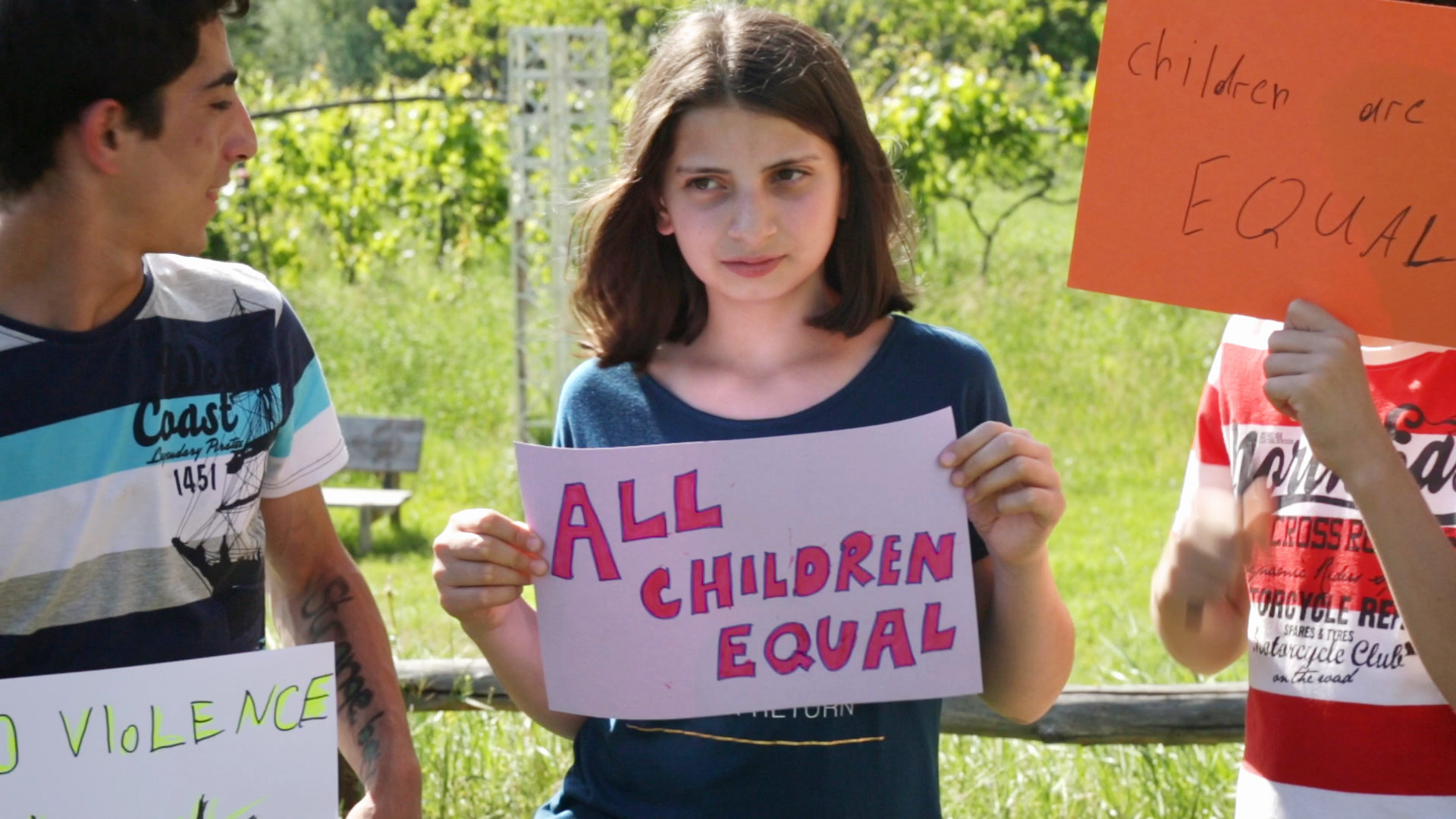"Three young people hold signs, one reads ""All Children Equal"""