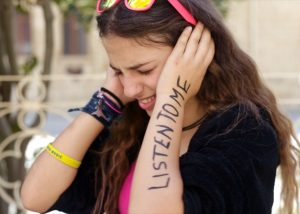 "A young person covers their ears, written on their arm in bold text are the words ""LISTEN TO ME"""