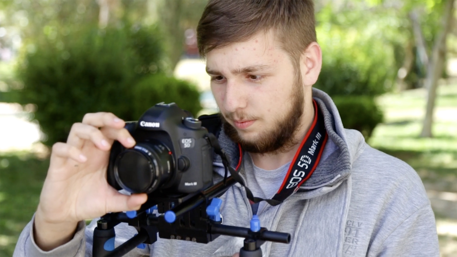 A young person uses a camera with a shoulder mount