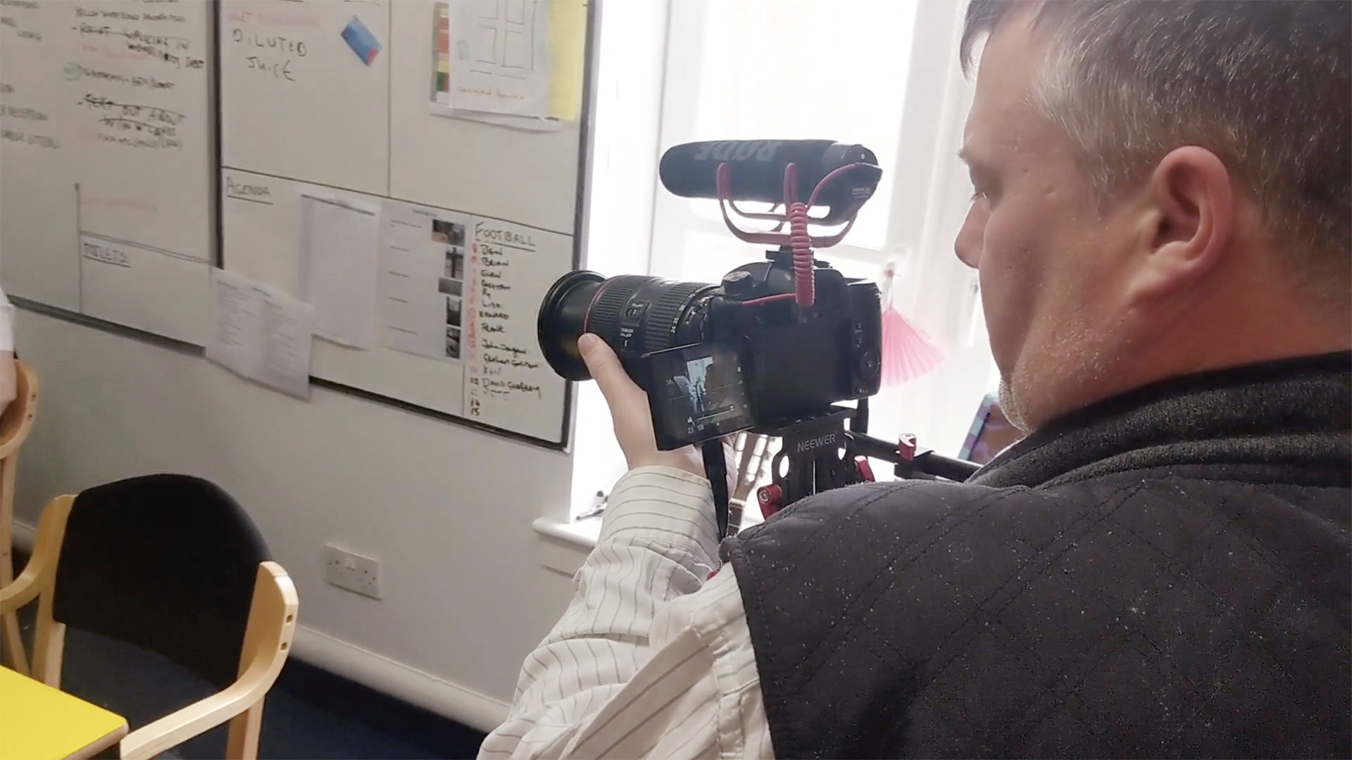 A member of Flourish House uses a handheld camera and shoulder mount