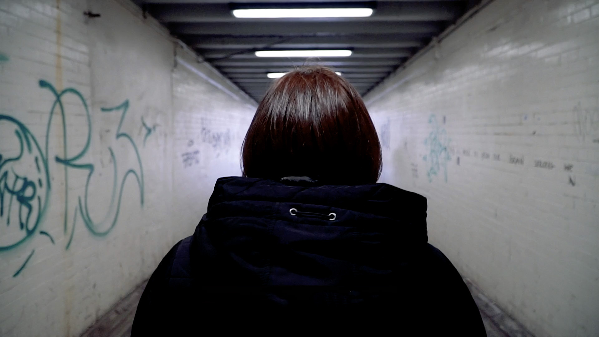 A participant in the Women's Aid project walks down a graffitied tunnel