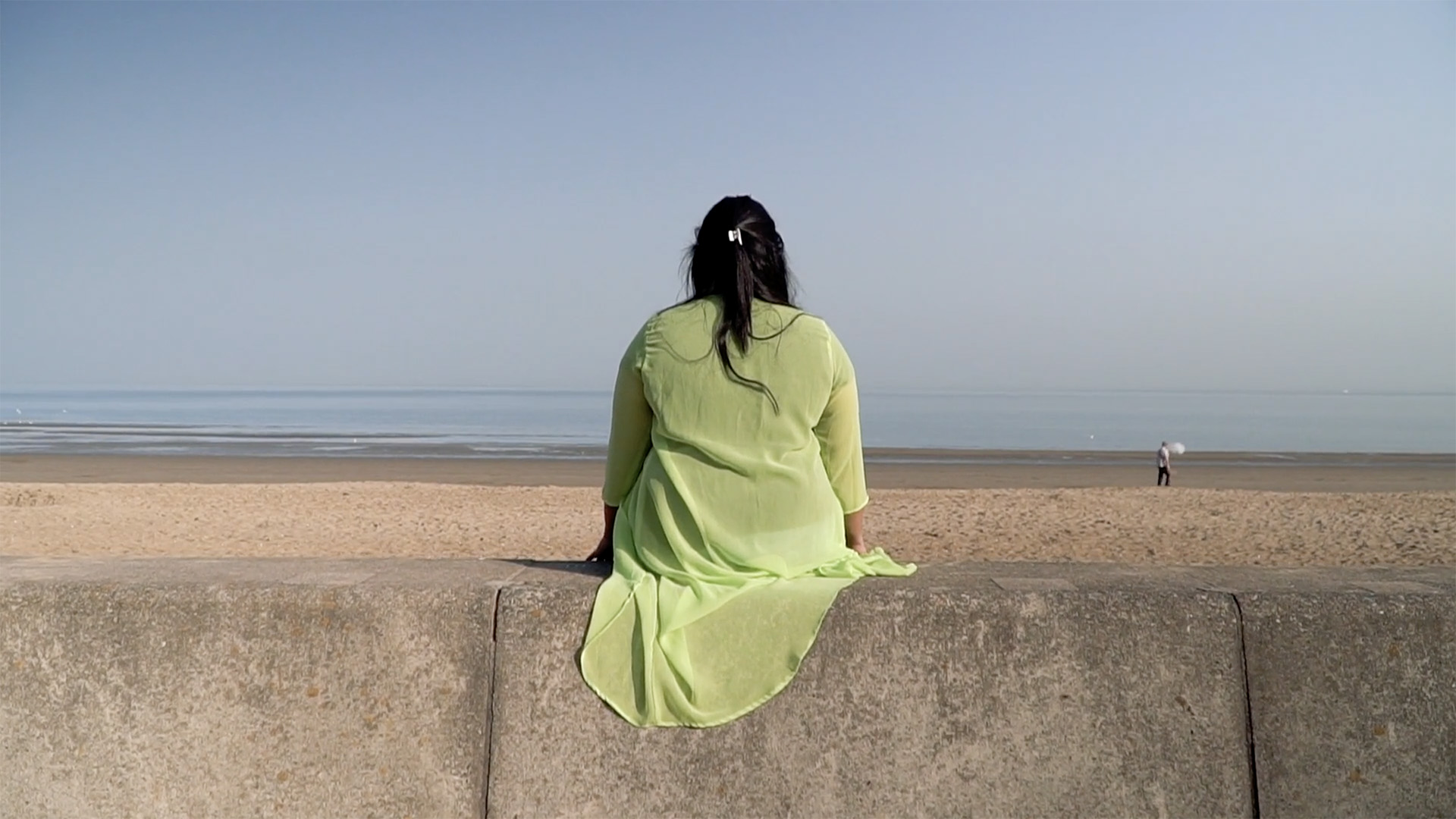 A participant in the Women's Aid project sits and looks out at the sea