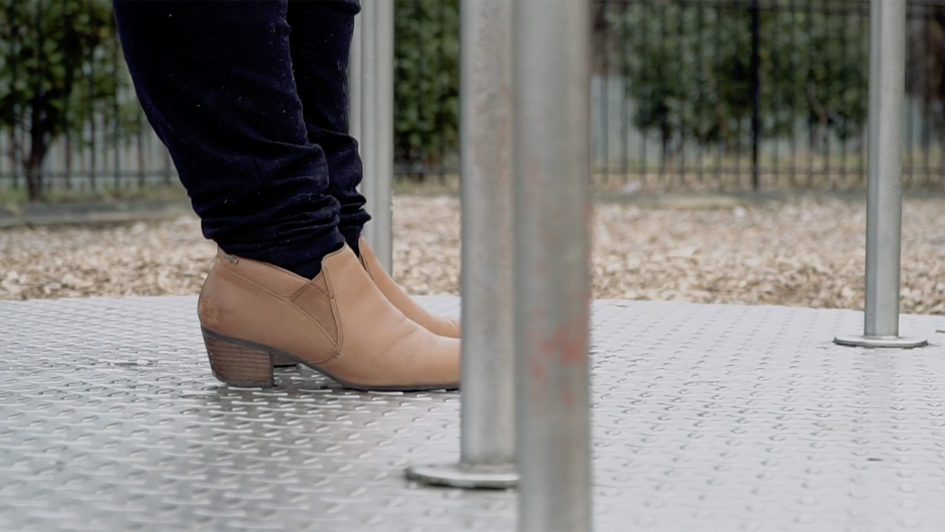 A close up on the shoes of a participant in the Women's Aid project, they are resting on a playground roundabout