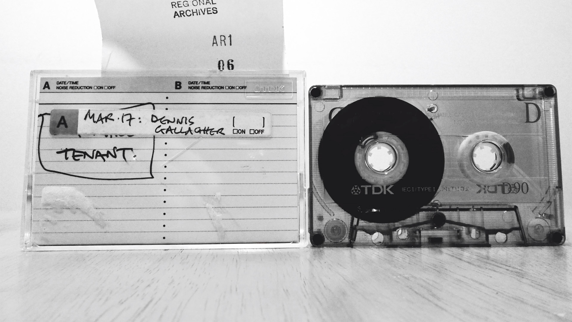 A cassette tape with labels indicating it is from a regional archive, black and white