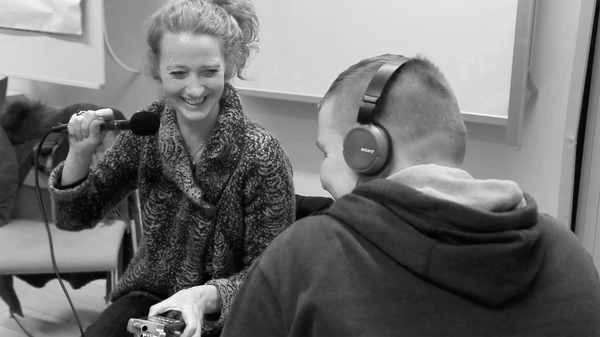 A Media Education staff member is smiling and holding a microphone while a participant in the foreground listens through headphones, black and white