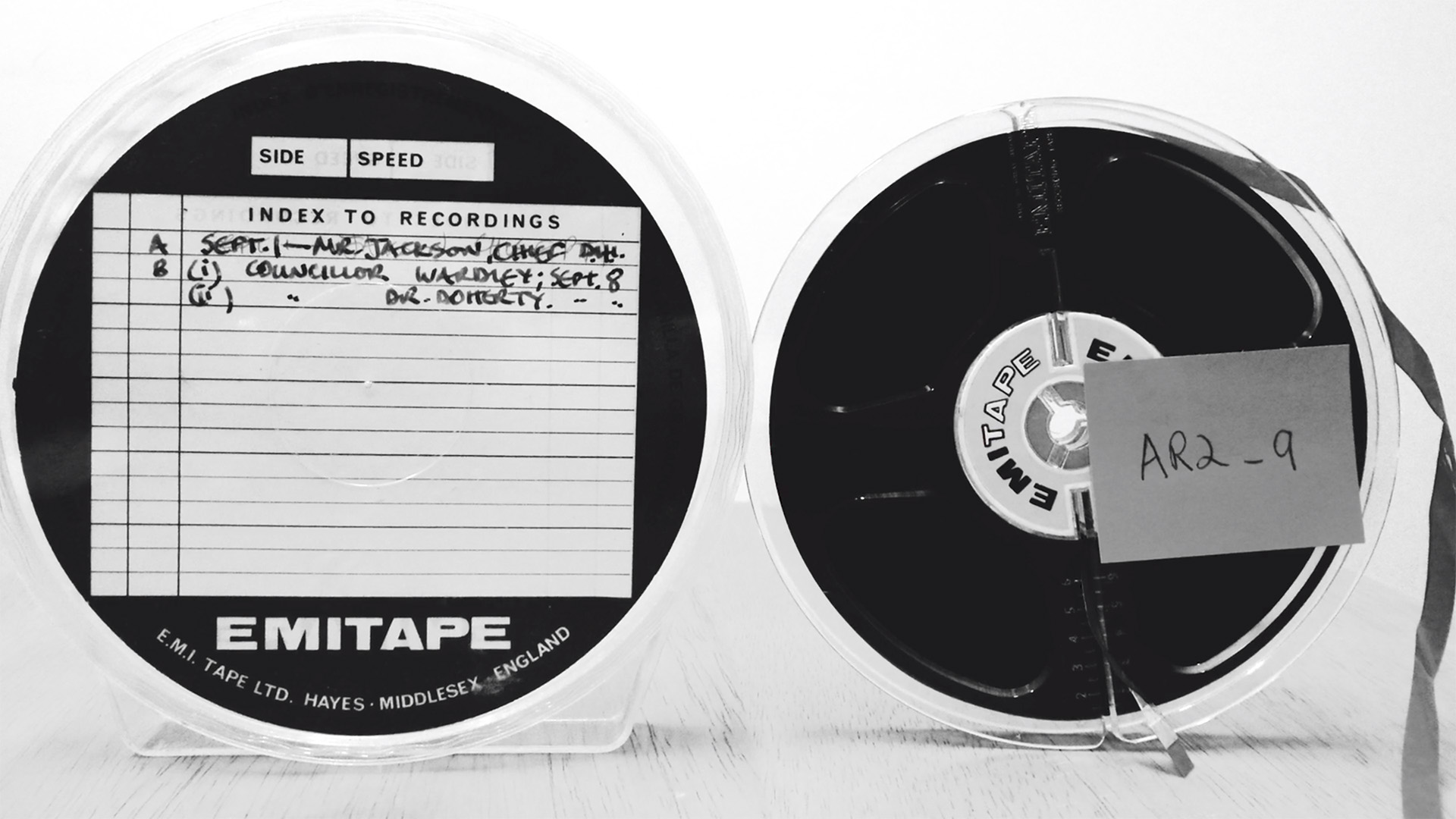 Two reel-to-reel cassettes with labels indicating they are from an archive, black and white