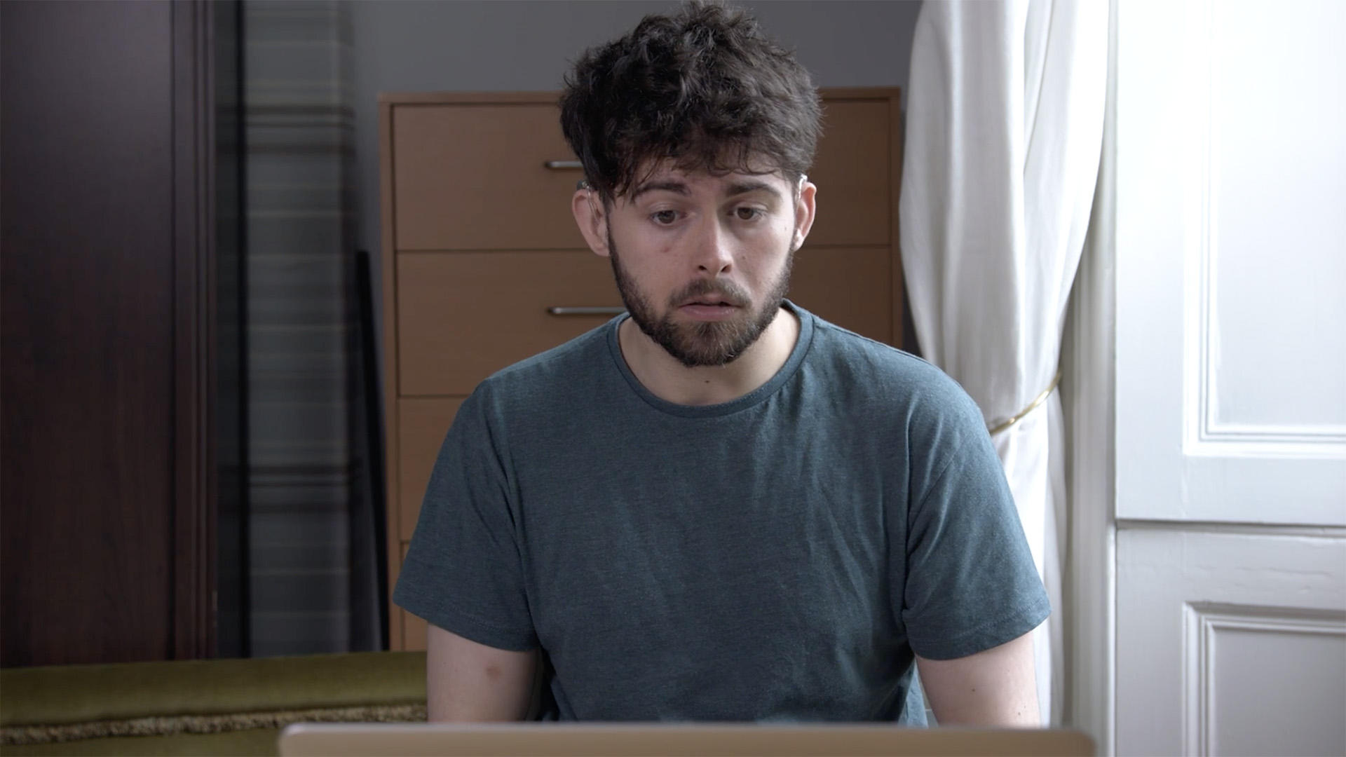 A person wearing hearing aids looks at a computer screen in their bedroom