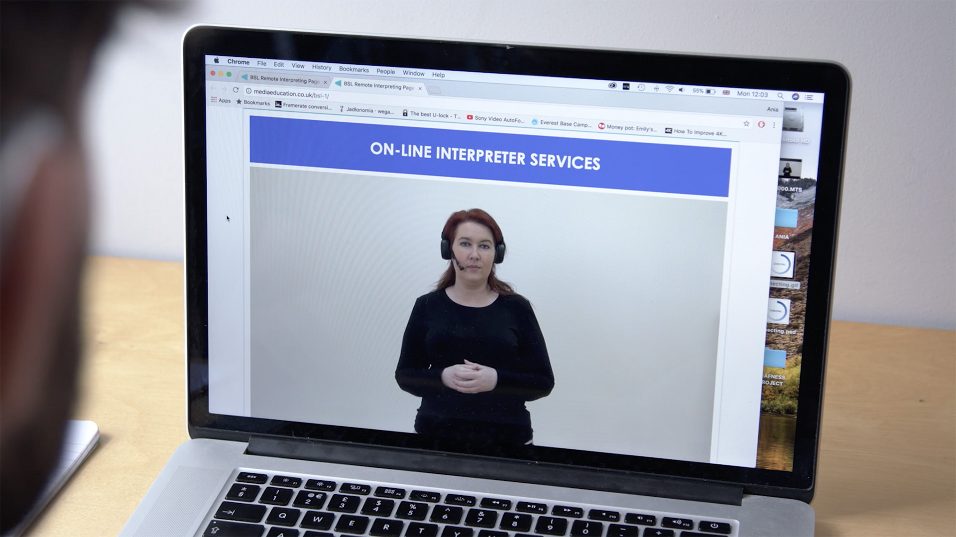 Over the shoulder of a person wearing hearing aids, a computer with an online BSL interpreter service open on screen
