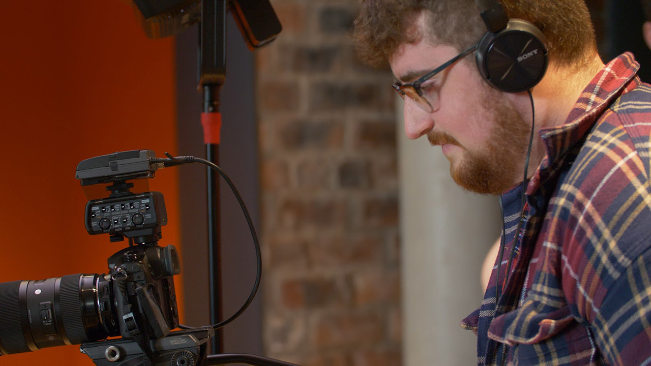 A young person wearing headphones monitors a camera during an interview