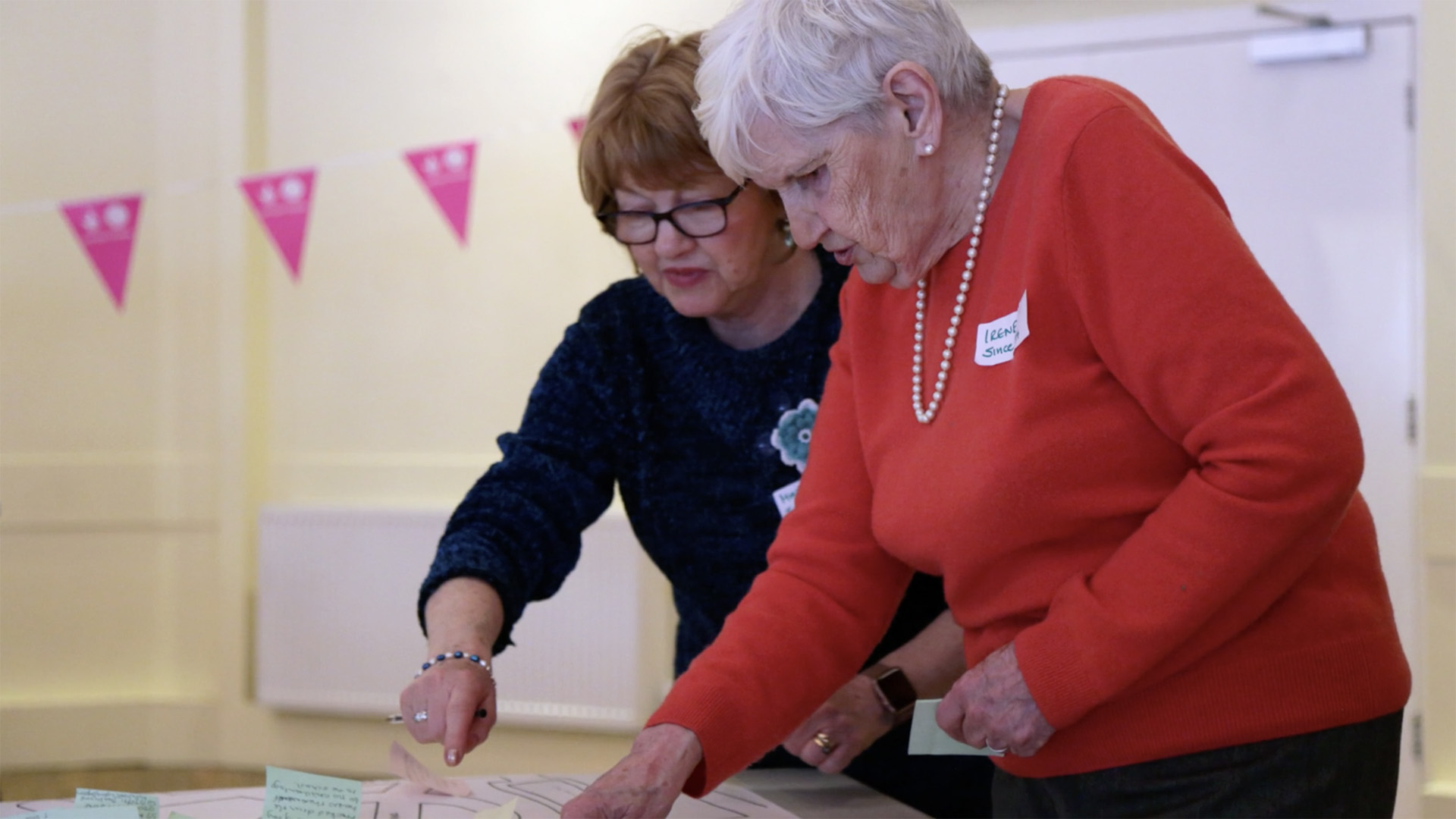 Two elderly people work together to place post-it notes on a hand drawn map